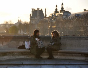 Two girls admiring their purchases on Pont Neuf.