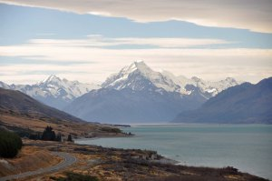Aoraki Mount Cook in the distance. Elevation 3754 metres, the highest peak in the Southern Alps. And we are driving there. See how the mountains are framed between the clouds and the lake-frontage. Beautiful.