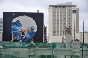 A ballerina from Swan Lake is being sprayed onto a wall. You can see the artist working from the cherry-picker.