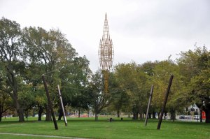 A suspended sculpture of a steeple hangs in Latimer Square. Beyond the trees is the Transitional Cathedral.