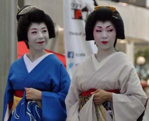 A double portrait of Ryoka and Hinagiku as they stand on stage.