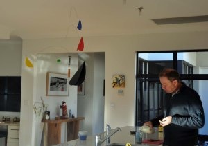 Matthew makes tea in this photo of our mobile. (A small Clare Reilly painting hangs in the background.)