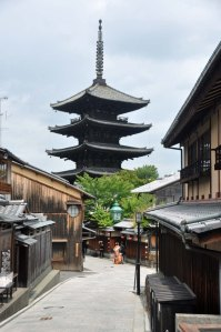 In the distance, a bride and groom pose under the Yasaka Pagoda.