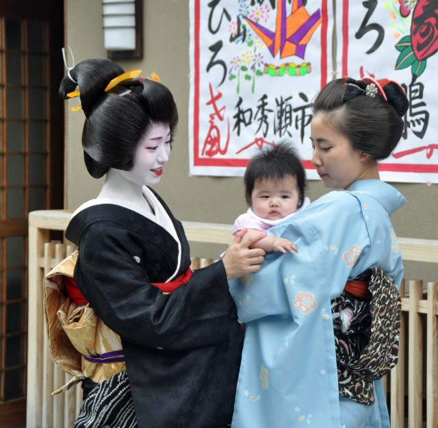 Kimihiro with her sister, Kimitoyo and a baby.